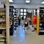Photo of people looking at several rows of books in the used book area at the library