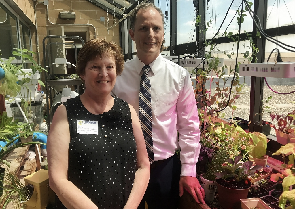 Rochester Garden Club member Susan Gerrits and Teacher Don Wilson from Stoney Creek in the green house with the grow lights