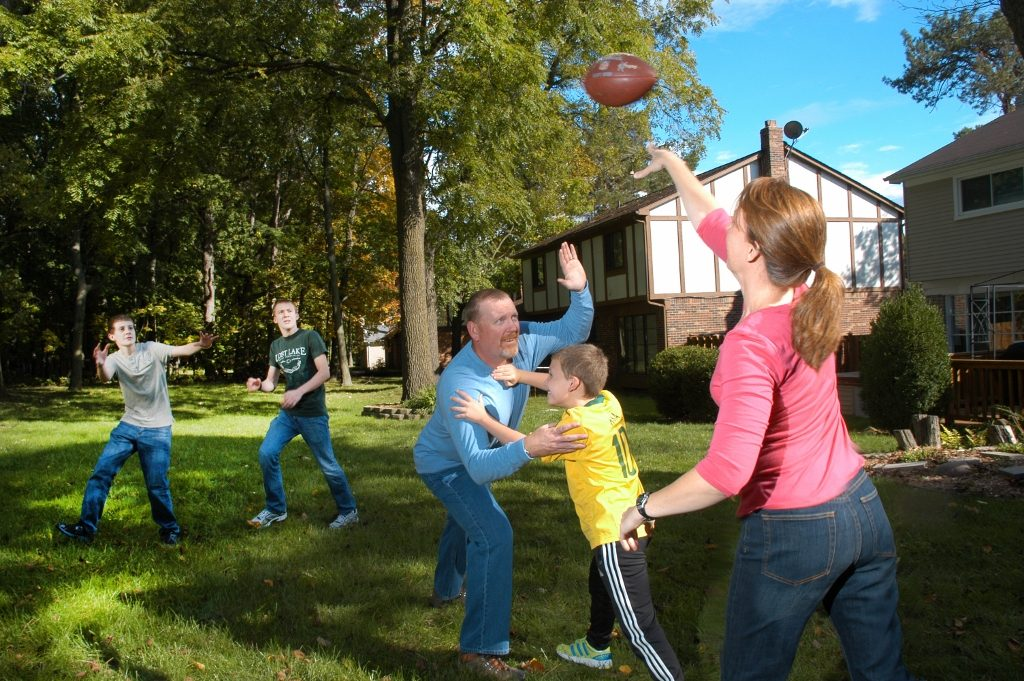 Family playing football in a front yard in Rochester Hills