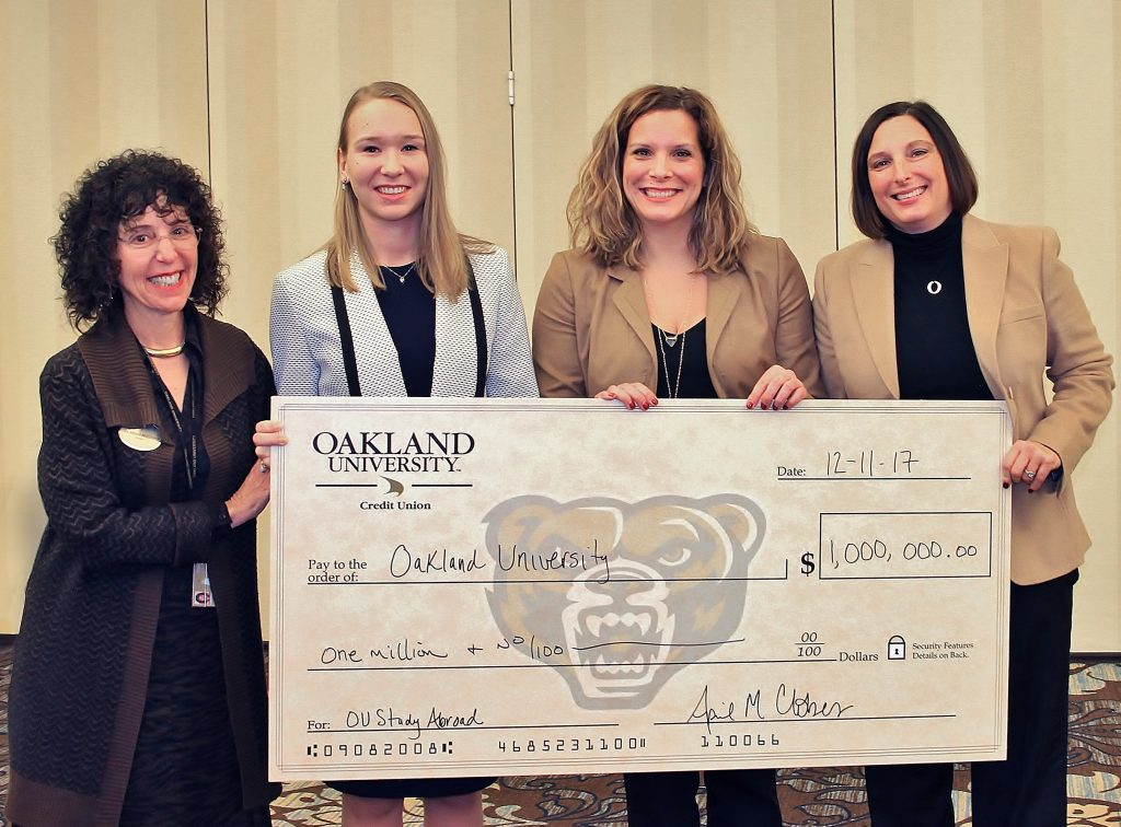 OU president Ora Pescovitz and OU study abroad student Natalia Boyko receive a ceremonial check from OUCU leaders Sara Dolan, CFO and April Clobes, president and CEO during the December 11, 2017 Oakland University Board of Trustees meeting