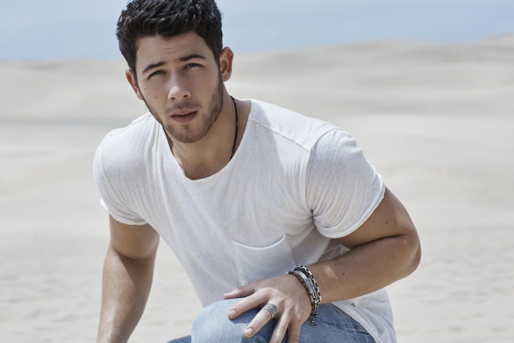 Photo of Jonas in plain white t-shirt and jeans kneeling down