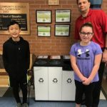 Fifth-grade North Hill Helpers, Jaesong and Madison, pose with North Hill Principal Dave Murphy in front of their new recycling bins