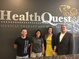 Four staff members pose for a photo under the HealthQuest sign inside their building