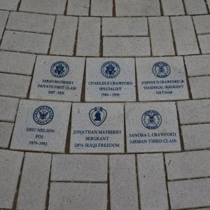 Photo of six brick pavers in the walkway around the tribute