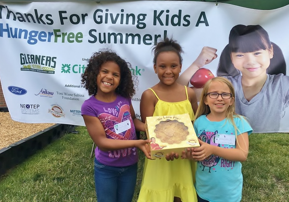 Three kids pose for a photo holding a boxed pie