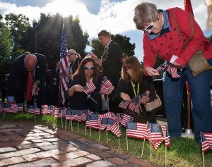 Residents plant small flags in the lawn near a brick walkway