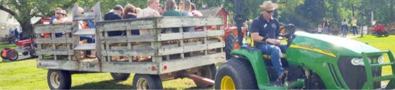 Large tractor pulls a wagon full of people