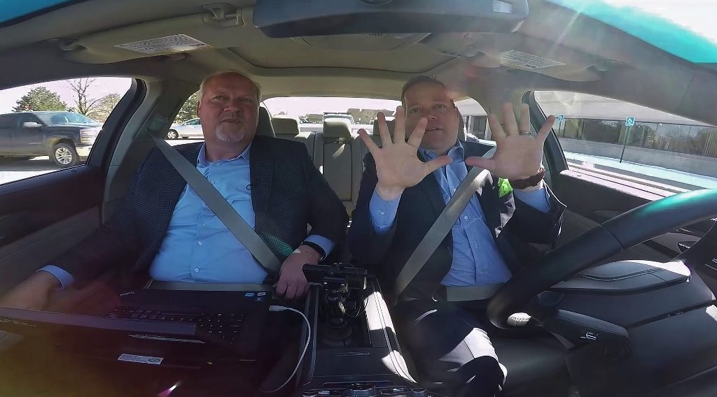Barnett in a test car holds his hands up in the air showing the car driving itself