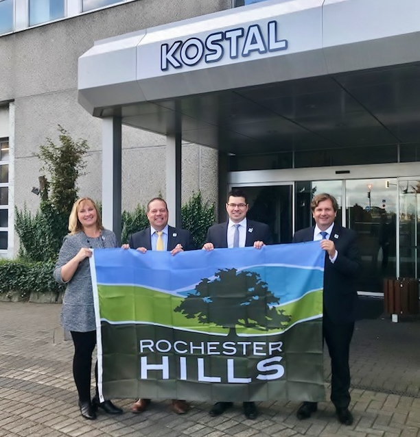 Kostal representatives and Mayor Barnett hold a Rochester Hills flag infront of the KOSTAL builing in Germany