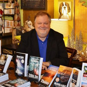 A photo of the author seated at a table with his books on display at a public book signing event