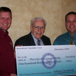 The three men hold a large check for $100,000 made out to the city of Rochester Hills