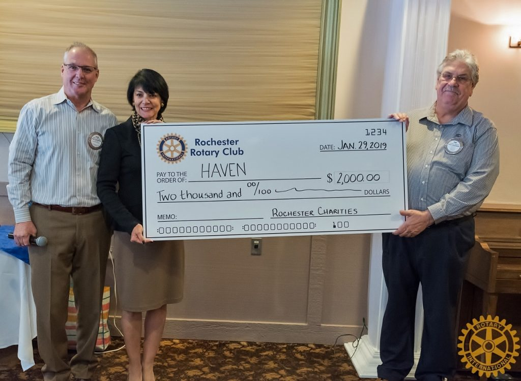 Rotary Members pose for a photo with the poster size check to HAVEN