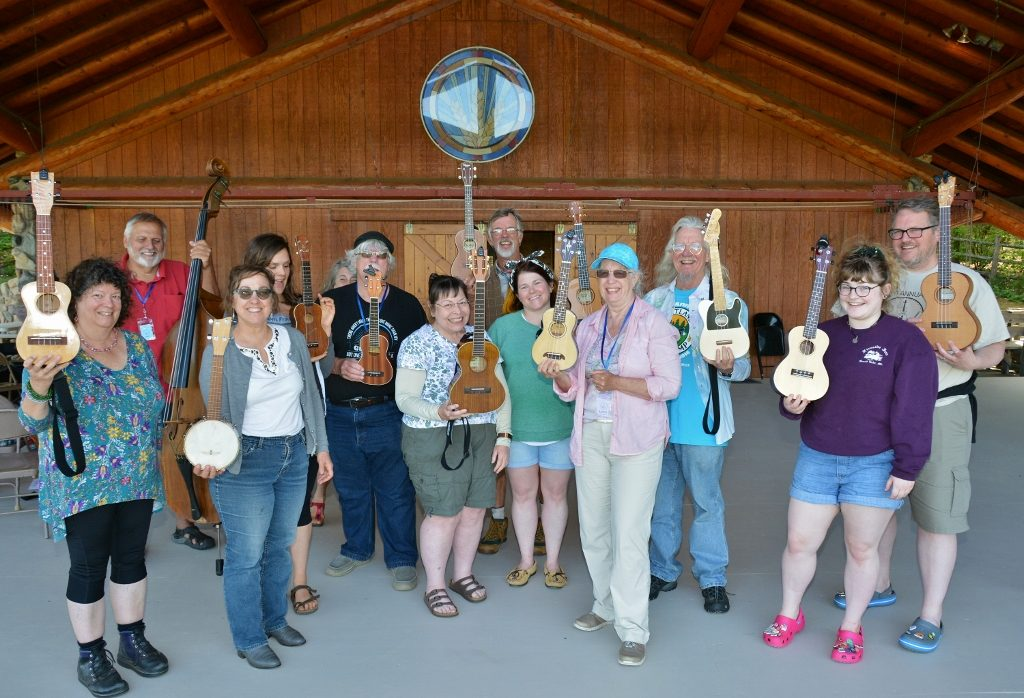 A dozen people stand on stage holding their ukulele