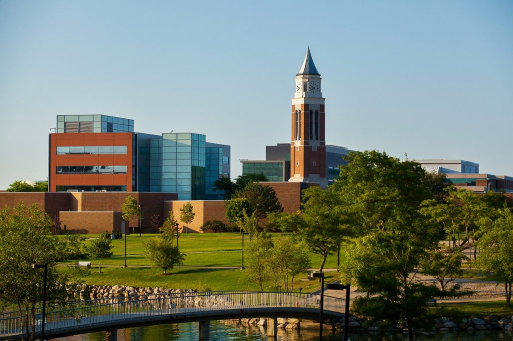 A sunny day photo of the OU campus showing the walking bridge over a small lake and the clock tower in the background.